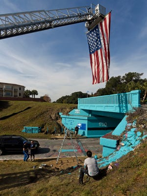 Staff from Escambia County EMS, firefighters and volunteers, help paint the graffiti bridge Sunday, December 3, 2017 in honor of EMS trainer Kara Zaremba who passed away from cancer.
