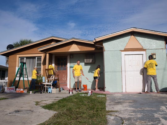 Hertz employees paint a house during a day of service