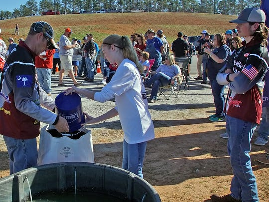 Westide High fisherman Thomas Hubbard (right) watches the competition at weigh-in Feb. 19 as his partners father Tommy Wurst (left) and sister Madison Wurst (center) fill up a fish catch bag.