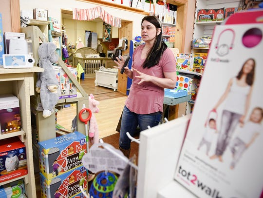 Adelle Starin, owner of Baby's on Broadway, shows some