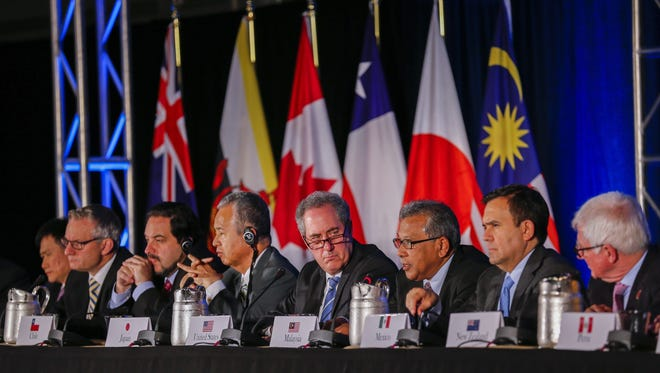 United States Trade Representative Michael Froman (center) is flanked by international counterparts during the closing press conference after an agreement was reachef by twelve Trans-Pacific Partnership (TPP) member countries, in Atlanta, Georgia, n Oct. 5, 2015