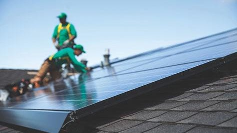 A solar panel is installed on the roof of a home by SolarCity employees.