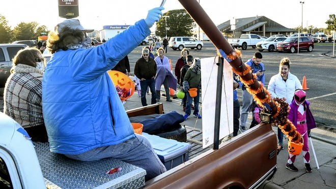Ron Whited, left, uses a pair of tongs to hold a piece of candy to load into a tube to send it down to a trick or treater's bag Saturday at the Clarion Inn parking lot.  Whited and his wife, Cathy, sat on a tool box at one end of their pickup's bed to provide social distancing at the Kansas Kruisers Trunk and Treat event.