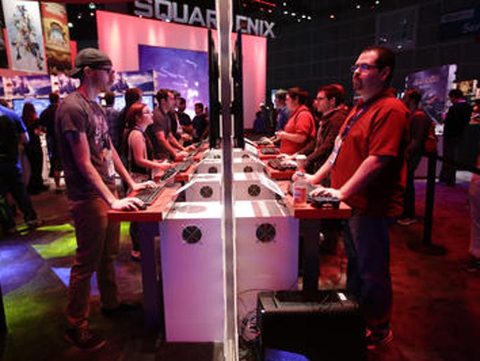People play a video game at the Square Enix booth at the Electronic Entertainment Expo on Thursday in Los Angeles.
