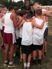 The ECS middle school boys cross country team praying with Coach John Roelofs before the championship race.