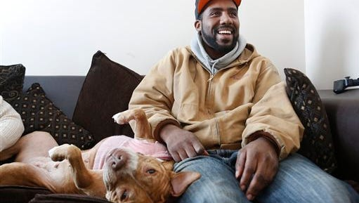 In this Monday, Jan. 26, 2015 photo, Tony Byrd Jr., sits on the couch with his 11-year-old American pit bull terrier named Mamma at their home in Port Clinton, Ohio. Mamma met a suspect at the door and defended her family by attacking the would-be burglar.