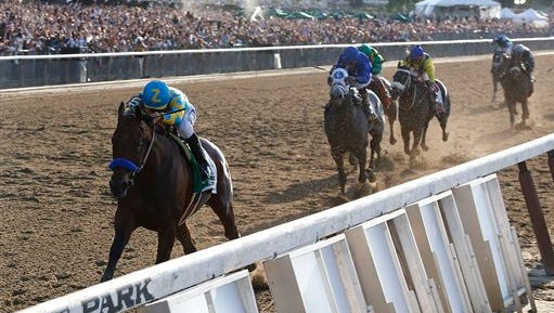 American Pharoah (5) with Victor Espinoza up leads the pack as he approaches the finish line during the 147th running of the Belmont Stakes horse race at Belmont Park, Saturday, June 6, 2015, in Elmont, N.Y. American Pharoah won to be the first horse to win the Triple Crown since Affirmed did it in 1978. (AP Photo/Julio Cortez)