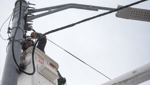 Xtreme Powerline Construction journeyman lineman Dan Stein finishes putting a new LED streetlight at the corner of East Davison and Conant in Detroit on Wednesday, March 4, 2015.