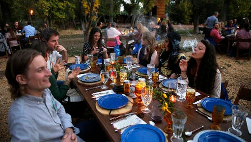 FILE - In this Oct. 2, 2016, file photo, diners smoke marijuana as they eat dishes prepared by chefs during an evening of pairings of fine food and craft marijuana strains served to invited guests dining at Planet Bluegrass, an outdoor venue in Lyons, Colo. Chefs and pot growers trying to explore fine dining with weed face a legal gauntlet to make pot dinners a reality, even where the drug is legal. Denver has approved a first-in-the-nation law allowing people to use marijuana in bars and restaurants. Denver voters weighed in on Proposition 300 as eight other states legalized marijuana for medical or recreational purposes last week.