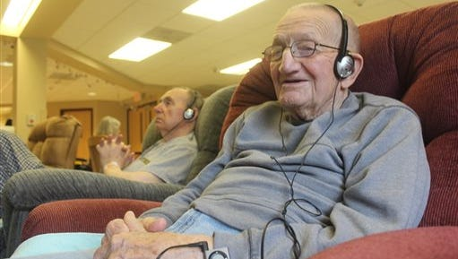 In this photo taken in Union Grove, Wis., Mike Knutson, 96, smiles as he listens to music on an iPod. He is part of a study through the University of Wisconsin-Milwaukee that is looking at whether mood and  behavior is altered when dementia and Alzheimer's patients listen to a personalized set of music.