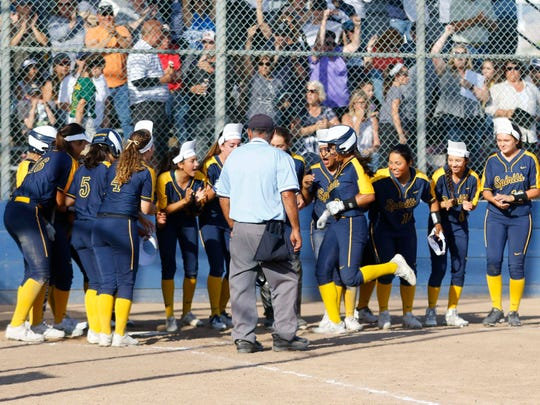 Notre Dame's Alexia Torculas is greeted at home after hitting a solo home run in the bottom of the fifth inning.