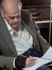 Richard Bellak writes musical notes by hand.