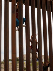 Children from Anapra, Mexico, climb a section of border