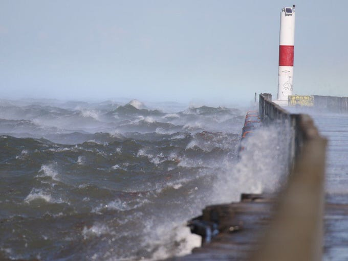 Waves crash against the pier in Charlotte during the