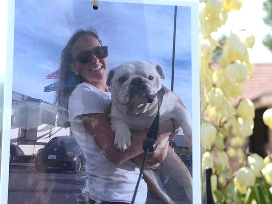 A photo hung from a stop sign on Plumb Lane and Krupp Circle shows Katie Weingartner holding her bulldog. The photo was taken by her friend Sierra Donohue. Weingartner died June 9, 2017 after she was hit by a car while walking her friend home.