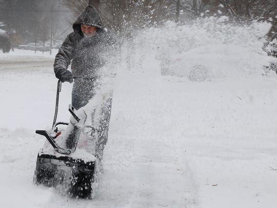 Don Jenkins of Pompton Lakes clears snow from the walk in front of his mother-in-law's home in Pompton Lakes after the heaviest part of the snowfall.