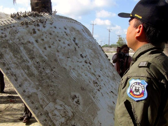 A Thai Royal Air Force officer inspects a piece of