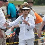 Debbie Naylor, left, escorts retired Navy Chief Petty Officer Charlie Jenkins to seat in the spectators bleachers to view the Blue Angels practice along the flight line behind the National Naval Aviation Museum Tuesday morning April 27, 2016. Naylor, a volunteer at the museum with more than 2400 hours of service, and still works a regular job as a flight attendant.