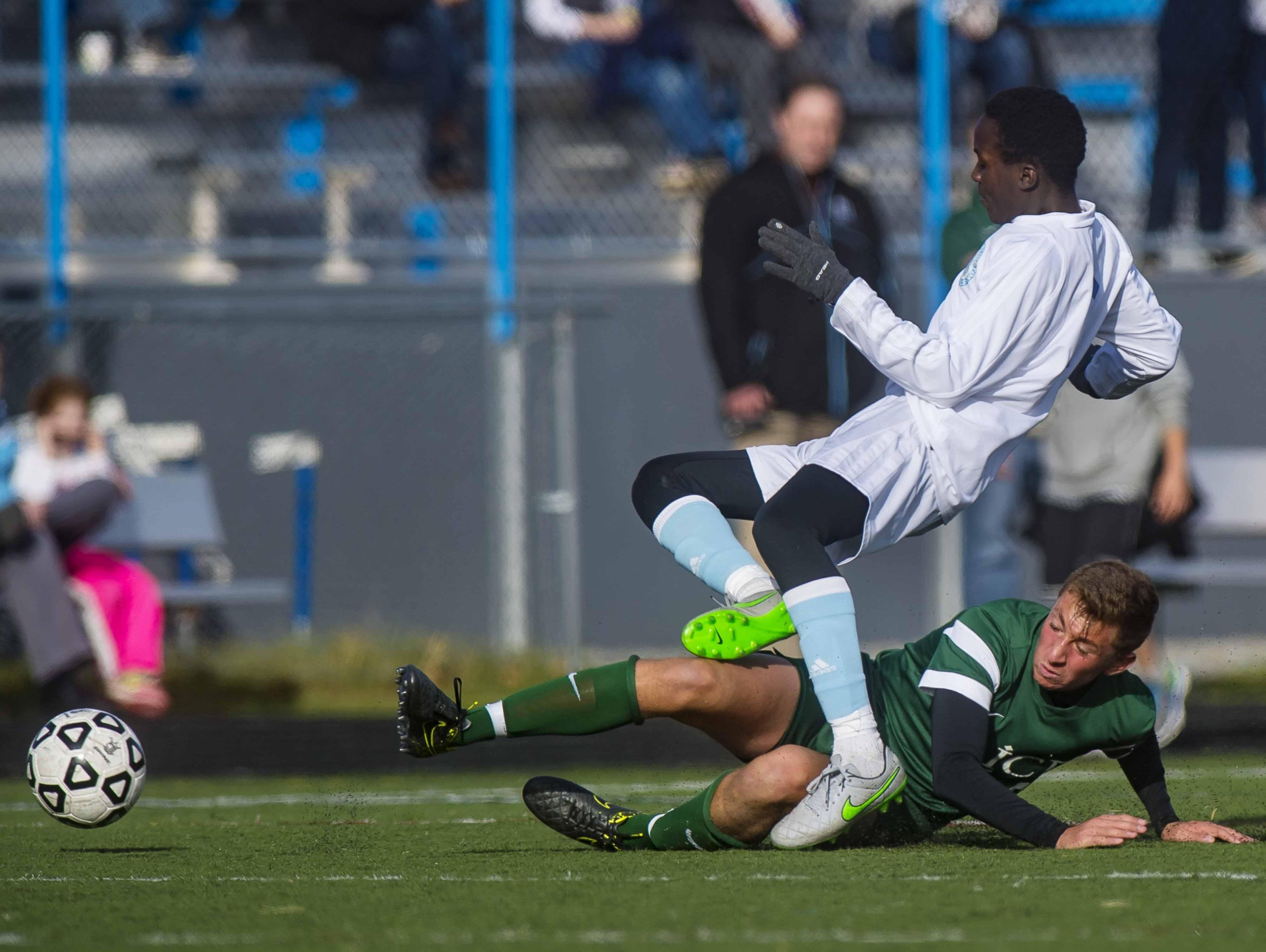 South Burlington's Amza Issa is tackled by Rice Memorial's Brent McKeown in South Burlington on Tuesday in the Division I high school boys soccer semifinals.
