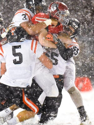 St. Cloud Tech's Trent Meyer, 5, Brevyn Spann-Ford, 3, and Josh Mendel, 55, tackle Elk River's Jon Suchy during the first half of the Section 6-5A championship game Friday, Nov. 3, in Buffalo.