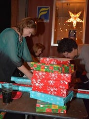 Volunteers wrap gifts at the United Way of Asheville and Buncombe County. The United Way is hosting book and gift drive for middle school youth. It is one of many charities in town collecting holiday gifts for people in need.
