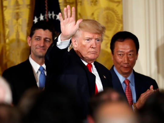 President Donald Trump waves after he announced last