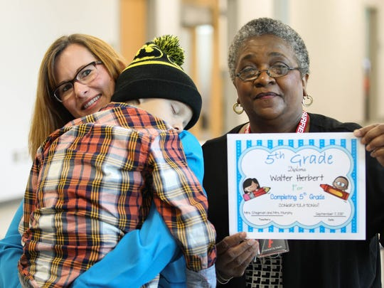 """Walter """"SuperBubz"""" Herbert completes multiple grades of school in one day at Fairfield Central Elementary school on Thursday, Sept. 7, 2017. Walter graduates from the fifth grade with Principle Karrie Gallo (left) and teacher Sandra Stegman."""