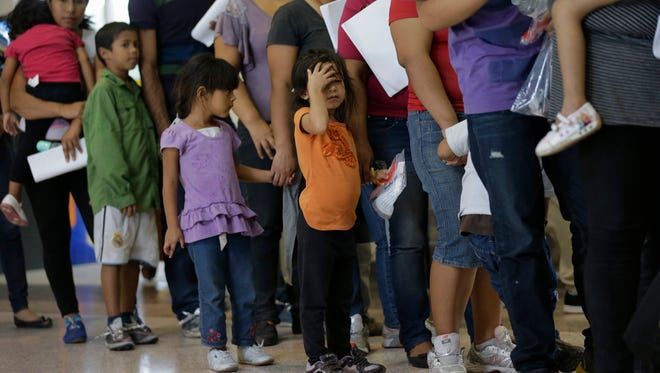 In this June 20, 2014, photo, immigrants who entered the U.S. illegally stand in line for tickets at the bus station after they were released from a U.S. Customs and Border Protection processing facility in McAllen, Texas. Hundreds of families and children from Central America caught traveling alone in recent weeks across the Mexican border told U.S. immigration agents they made the dangerous journey in part because they believe they will be permitted to stay in the United States and collect public benefits, according to internal intelligence files from the Homeland Security Department.