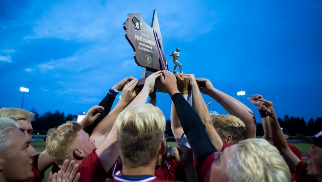 Muskego players hoist the WIAA summer championship trophy after the Warriors beat Pius XI, 2-1, in 8 innings in the title game on Friday.