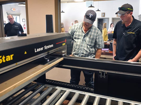 Lance Jackson, right, watches as Austin Keesee demonstrates the laser etching system at his new business, Austin Stone and Monument. The company also does computerized sand blasted designs in headstones and other monuments and signs.
