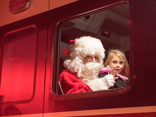 Seven-year-old Chloe Hoard arrives in a fire truck with Santa and Mrs. Claus.