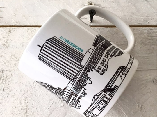 a coffee mug decorated with a rendering of downtown Rochester.