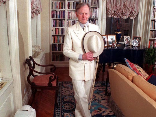 Wearing his trademark white suit author Tom Wolfe poses in his New York home Dec. 22 1998.
