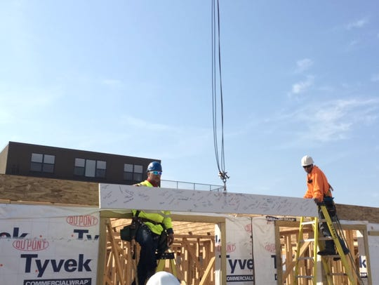 Workers put a signed beam in place to make CityDeck