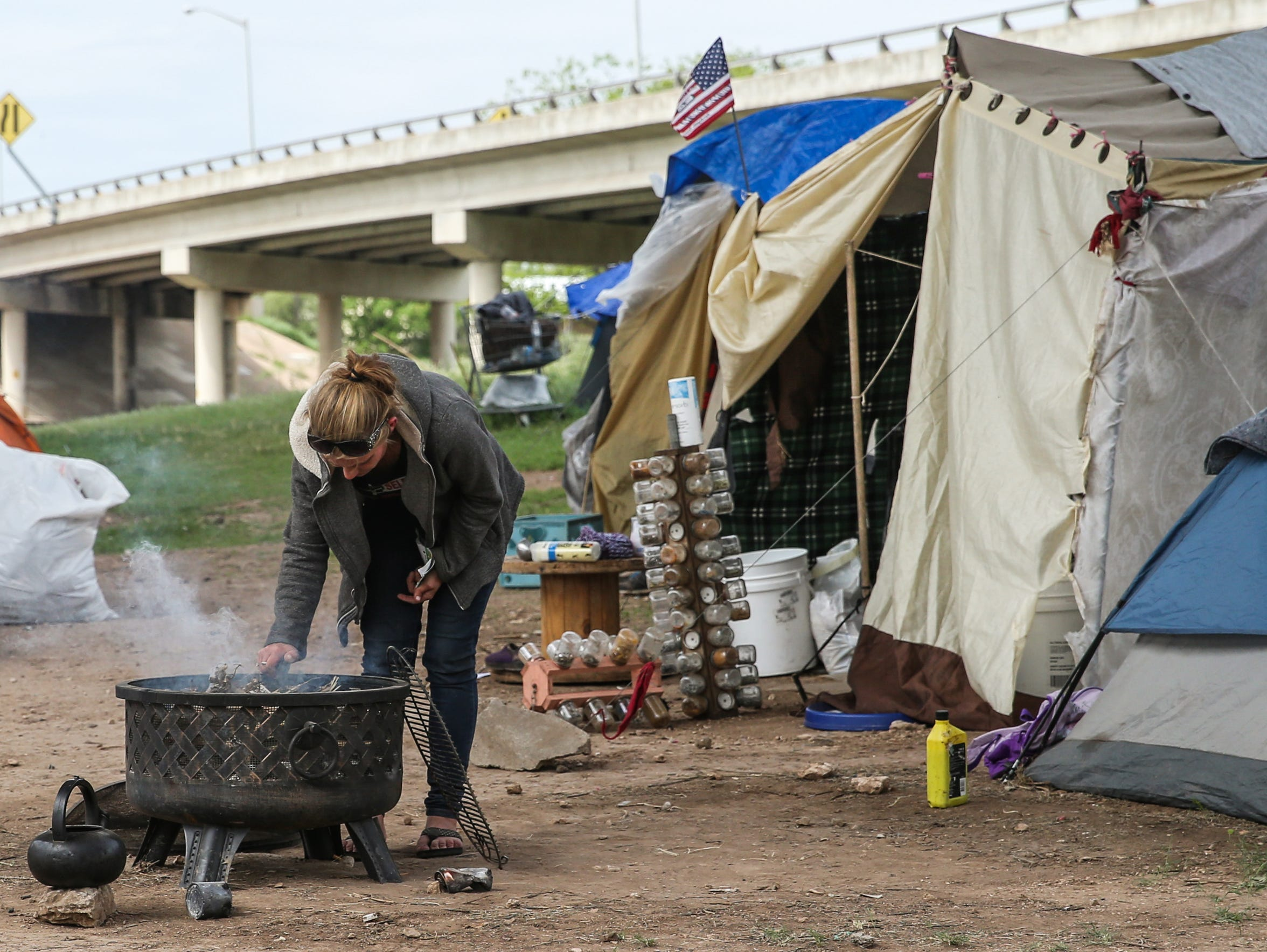 Heidi Martinez builds a fire at the tent city under