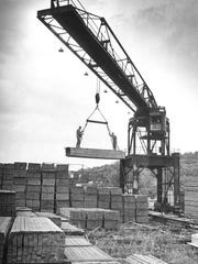 Reginald Rifenburgh, left, and Robert Hamill ride a pile of lumber as it is lifted by a crane at the A.C. Dutton Lumber Co. yard in Poughkeepsie on Oct 9, 1966. The crane is operated by Jack Perkins, a 43-year employee of the firm.