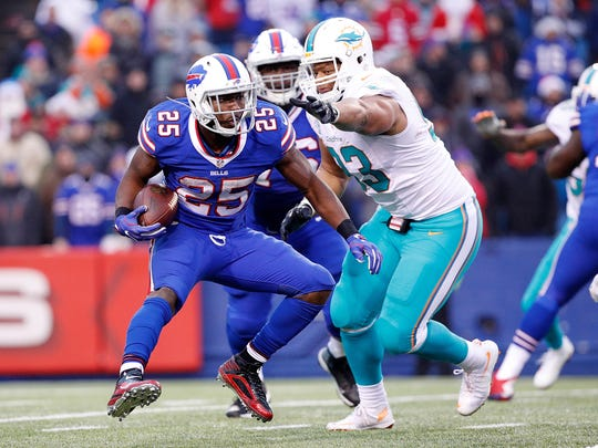 Buffalo Bills running back LeSean McCoy (25) misses a tackle by Miami Dolphins defensive tackle Ndamukong Suh (93) during the second half at New Era Field. The Dolphins beat the Bills 34-31 in overtime.