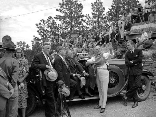 Gutzon Borglum, noted sculptor engaged in carving heroic heads of famous Americans on Mount Rushmore, points out details of the mammoth project to President Roosevelt (seated, in car) in Rapid City on August 31, 1936. Others in the group, left to right, Anne Senator Bulow and Governor Berry of South Dakota, and Franklin D. Roosevelt, Jr. (AP Photo)