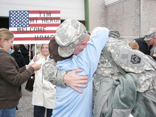 Spc. Tim Albright hugs his son, Caleb, 12, after arriving at the Pennsylvania National Guard Armory in Avon in Oct. 2008 following his trip home from Afghanistan. Albright s wife, Melissa, is at left.