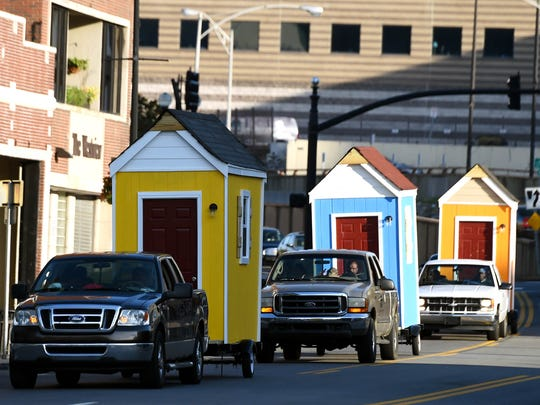 Six micro homes on trailers travel  down Nashville streets to a homeless camp.
