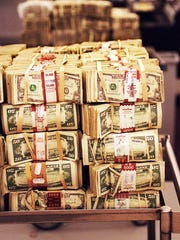 Bundles of 50-dollar bills sit in the currency processing area of a bank vault.