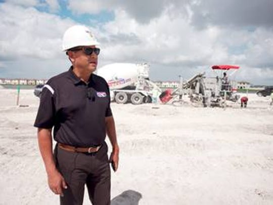 Luis Garcia, owner of Adonel Concrete, on site at a construction site, with one of his trucks behind him.
