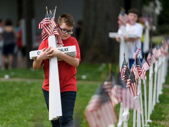 North Middle School student Brandon Pulliam walks through Central Park as he works with other students to put up Memorial Day crosses in honor of deceased Henderson County veterans, Wednesday morning, May 9, 2018.