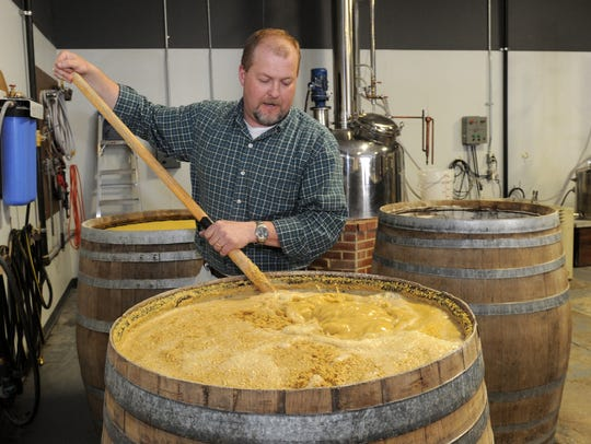 Tom Adams, owner and distiller of Seven Troughs Distilling Co., stirs the whiskey mash at the distillery in Sparks in 2014.