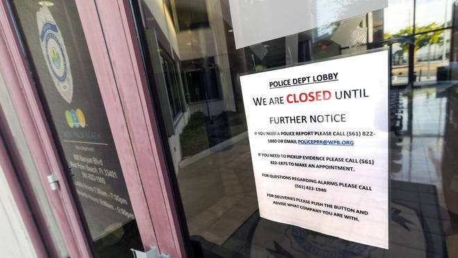 Signs on the doors to the West Palm Beach Police Department tell people what to do while the lobby is closed because of coronavirus Wednesday, March 18, 2020.
