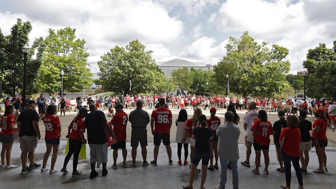 Ohio State football fans listen during a rally organized by parents of Buckeyes players outside the rotunda of Ohio Stadium.