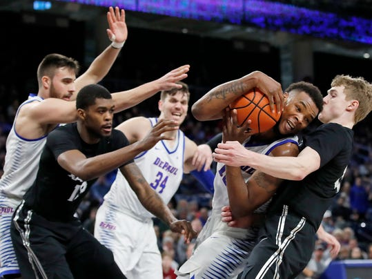 DePaul forward Tre'Darius McCallum, second right, crashes into Xavier guard J.P. Macura, right, as he grabs a rebound during the second half of an NCAA college basketball game Saturday, March 3, 2018, in Chicago, Ill. (AP Photo/Jim Young)