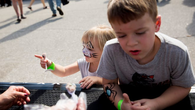 Ella Rexford, 2, and her brother Jaxon, 5, try a sampling of Tipsy Cow ice cream during the 24th Annual Taste of Bonita at Riverside Park on Sunday, Dec. 3, 2017, in Bonita Springs, Fla.