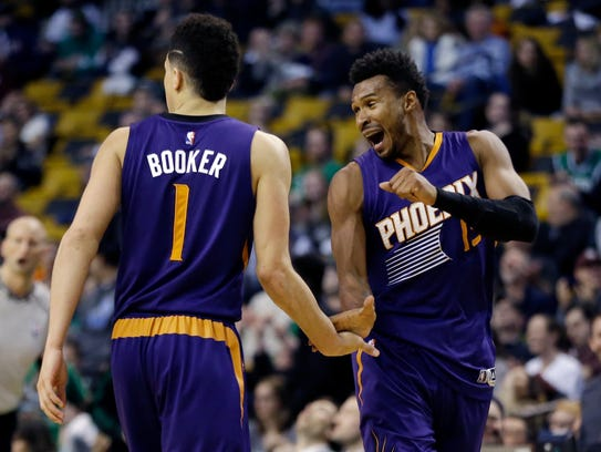 Suns guard Devin Booker is congratulated by Leandro Barbosa in the fourth quarter of Booker's 70-point game.