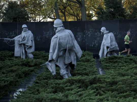 A man runs past the Korean War Memorial on the National